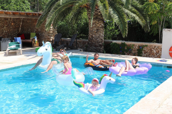 Photo of Taylor family relaxing on inflatables in pool